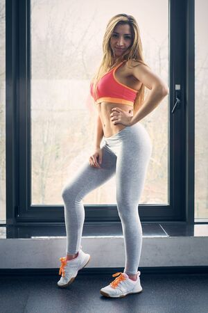 Fit girl wearing short top standing near the window in gym Stock Photo