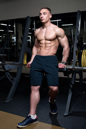 Muscular shredded shirtless man in the black shorts with watches stays on the silver bar in a gym