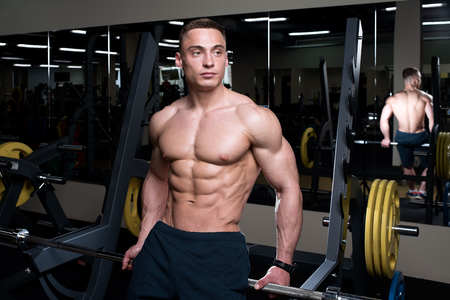 Muscular shredded shirtless man in the black shorts with watches sits on the bar in a gym