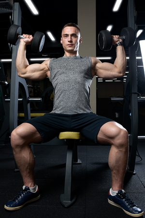 Muscular man doing dumbbell overhead