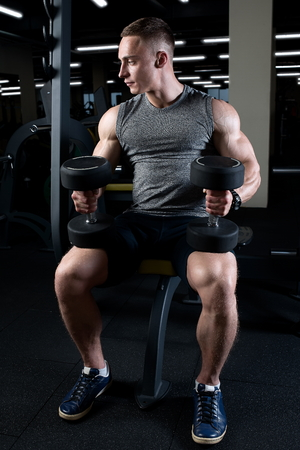 Muscular man with dumbbells sits on the bench in a gym