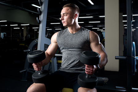 Muscular man with black dumbbells sits on the bench in a gym Stock Photo