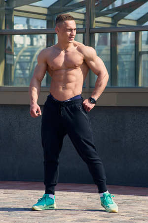 Muscular shirtless man in the black pants with watches poses on the street