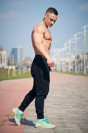 Muscular shredded shirtless man in the black pants with watches poses on the street
