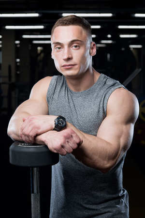 Muscular man with big arms poses in the gray shirt