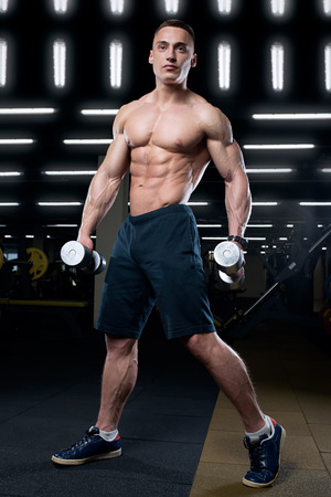 Muscular shredded shirtless man in the black pants with watches poses with two dumbbells in a gym