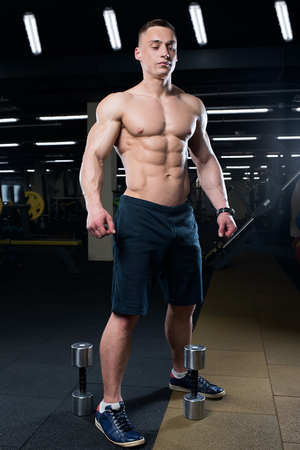 Muscular shredded shirtless man in the black shorts with watches stays with two dumbbells in a gym