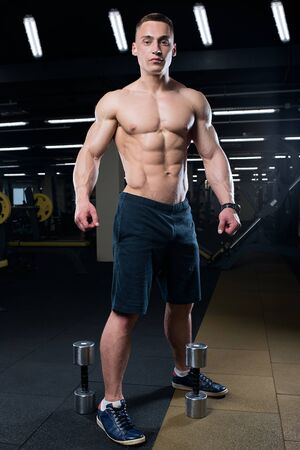 Muscular shredded shirtless man in the black shorts with watches stays with two dumbbells in a gym in the evening