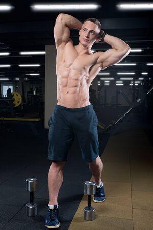 Muscular shredded shirtless man in the black pants with watches stretch with two dumbbells in a gym Stock Photo