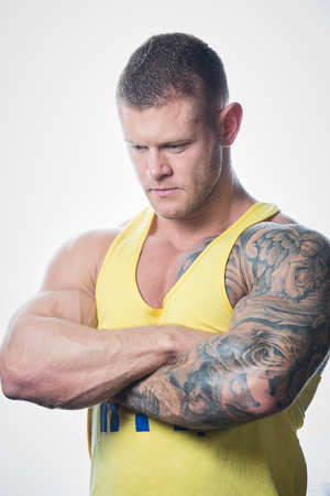 Muscular strong man with blue eyes and tattoo in the yellow tank top view looks down on the white background Stock Photo