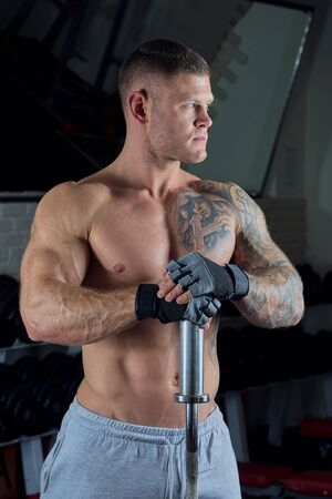 Muscular shirtless man with blue eyes and tattoo poses with barbell in gloves and gray pants in a gym