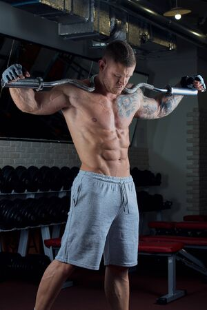 Muscular shirtless man with blue eyes and tattoo poses with EZ curl bar on the neck in gloves and gray shorts in a gym