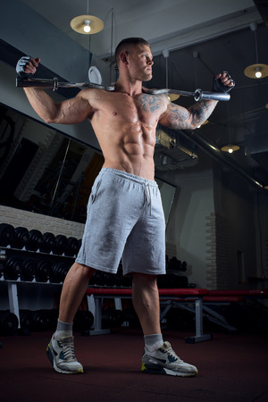 Muscular shirtless man with blue eyes and tattoo poses with EZ curl bar on the neck in gloves and gray shorts in full growth in a gym