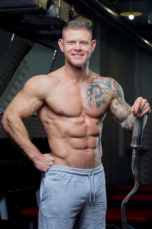 Muscular shirtless man with blue eyes and tattoo smiles with EZ curl bar in a gray pants in a gym