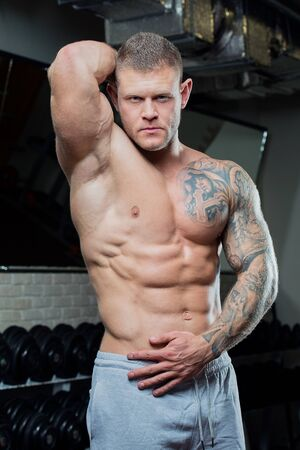 Muscular shirtless strong man with blue eyes and tattoo poses in a gray pants in a gym