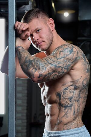 Muscular shirtless shredded strong relaxed man with blue eyes and tattoo poses on a power cage in a gray pants in a gym Stock Photo