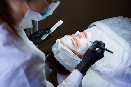 Vista lateral de una cosmetóloga que aplica peeling gommage en la cara de la niña. Un médico con mascarilla médica y guantes médicos desechables negros durante un procedimiento en un salón de belleza para la limpieza de la piel