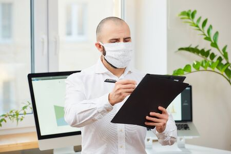 A man in a medical face mask against the coronavirus (COVID-19). An engineer with pen and a folder making notes at his workspace with computers and green plant in the background. Coronavirus quarantine.