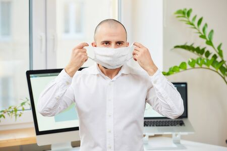 A man in a white shirt taking off a medical face mask against the coronavirus (COVID-19). A manager at his workspace with computers and green plants in the background. Coronavirus quarantine.