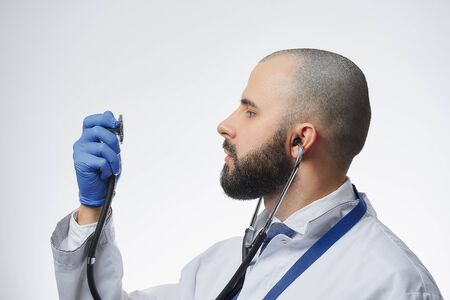 A doctor wearing a stethoscope looking at the head of it in his hand. A physician practitioner with a beard in a white lab coat and a blue tie.