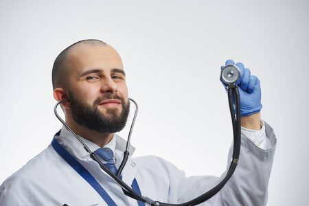 A happy doctor posing with a stethoscope in his hand in a blue medical glove. A physician practitioner with a beard in a white lab coat and a blue tie.