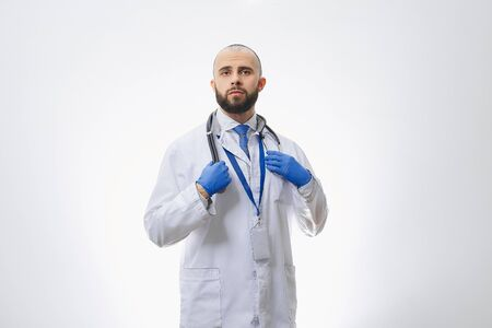 A doctor with a stethoscope and disposable medical gloves. A bald physician with a beard preparing to examine patients.