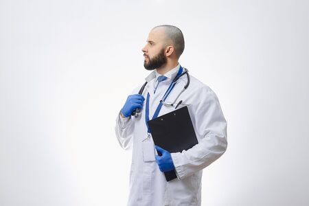 A doctor in disposable medical gloves with a stethoscope and a clipboard. A bald physician with a beard preparing to examine patients. 版權商用圖片