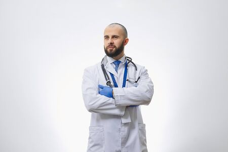 A serious doctor with arms crossed on his chest in disposable medical gloves with a stethoscope. A bald physician with a beard preparing to examine a patient.
