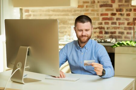A man with a beard wants to do online shopping and looks with anticipation at his credit card at home. A guy waiting to do an online payment on the internet on a desktop computer in his apartment.
