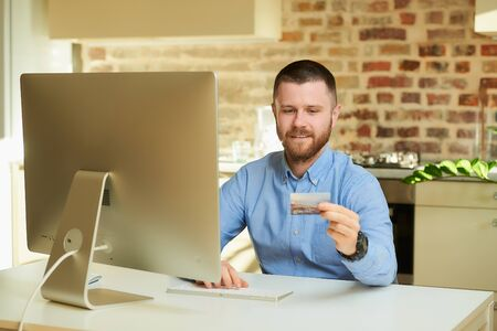 A man with a beard types a credit card number to do online shopping at home. A guy doing an online payment on the internet on a desktop computer in his apartment.