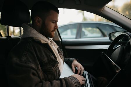 A young man with a beard opens his laptop computer to do business inside a comfort car. A guy stopped his car to immediately remotely solve tasks at work in social distance.
