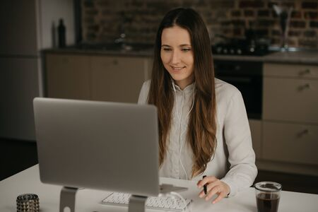 Remote work. A caucasian brunette woman with headphones working remotely on her laptop. A happy girl in a white shirt doing business at her home workplace.