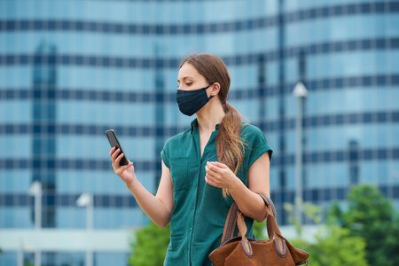 A young woman in a navy blue medical face mask to avoid the spread of coronavirus in the center of the city. A girl with long hair is reading the news on a smartphone in downtown.