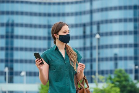 A young woman in a navy blue medical face mask to avoid the spread of coronavirus is holding her leather bag in the center of the city. A girl with long hair is using a smartphone in downtown.