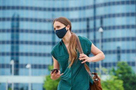 A young woman in a navy blue medical face mask to avoid the spread of coronavirus straightens her leather bag in the center of the city. A girl with long hair is holding a smartphone in downtown.