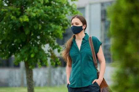 Woman in medical face mask walks between trees thrusting hand into pocket of trousers, holds a bag in downtown. Girl keeping social distance wears a protective mask to avoid the spread of coronavirus 免版税图像