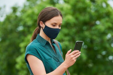 A side view of a young woman in a medical face mask is reading news on a smartphone while walking in the park. A girl in a protective mask keeping social distance to avoid the spread of coronavirus.