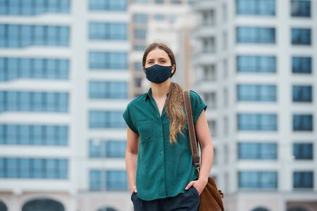 A portrait of a woman in a medical face mask is thrusting hands into pockets of trousers while walking in the center of the city. A girl in a protective mask keeping social distance on the street 版權商用圖片
