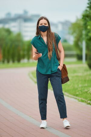 A pretty woman in a blue navy medical face mask reads news on a phone thrusting a hand into the pocket of trousers walks in the park. Girl keeping social distance wearing a protective face mask. 版權商用圖片