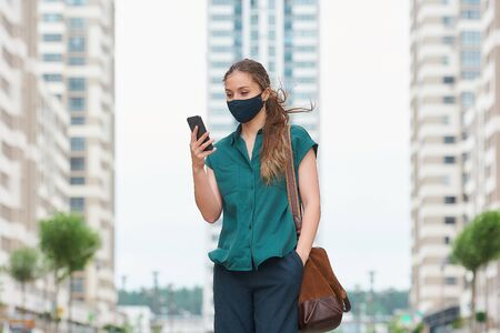 A young woman in a medical face mask reads news on her smartphone thrusting a hand into a pocket of trousers walks between skyscrapers. A girl keeping social distance wearing a protective face mask.