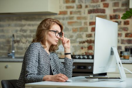 A woman in glasses works remotely on a desktop computer in her studio. A female boss searching for information at a video conference at home. A pretty female professor preparing for an online lecture.