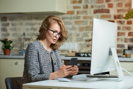 A young woman in glasses works remotely on a desktop computer in her studio. A female boss uses a smartphone during a video conference at home. A female student listening to an online lecture. Foto de archivo