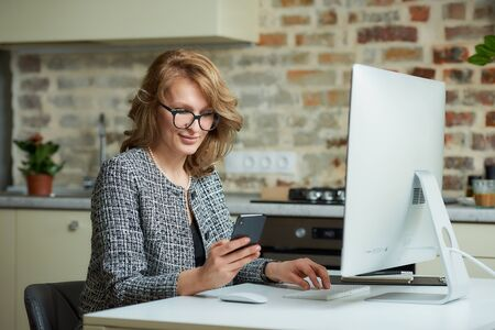 A woman in glasses works remotely on a desktop computer in her studio. A boss distracted by a smartphone during a video conference at home. A happy professor uses a cellphone before an online lecture