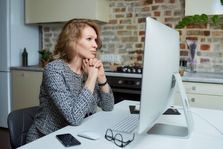 A young woman works remotely on a desktop computer in her studio. A lady sits arms crossed during a video conference at home. A female professor listening to student's answers on an online lesson.