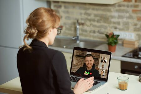 Back view of a businesswoman who speaks with colleagues during a video conference on a laptop. A female boss talks on a video call with her employees engaged in an online business briefing at home. Archivio Fotografico