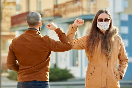 Elbow greeting to avoid the spread of coronavirus (COVID-19). Man and woman in medical face masks meet on the street with hands. Instead of greeting with a hug or handshake, they bump elbows.