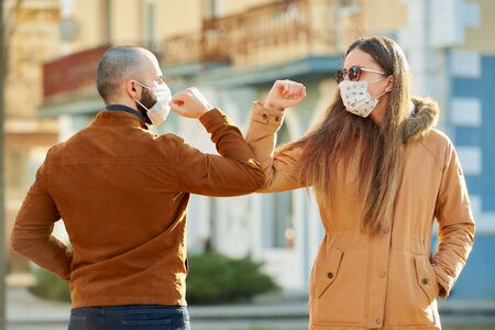 Elbow greeting to avoid the spread of coronavirus (COVID-19). A man and a woman in medical face masks meet on the street with hands. Instead of greeting with a hug or handshake, they bump elbows.