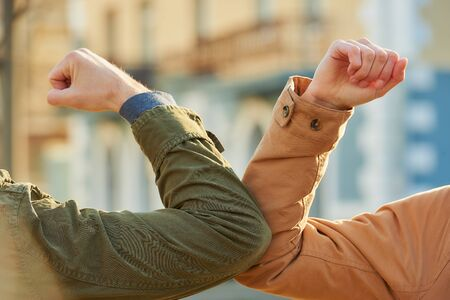 Elbow greeting to avoid the spread of coronavirus (COVID-19). Friends meet on the street with hands. Instead of greeting with a hug or handshake, they bump elbows instead. Stock Photo