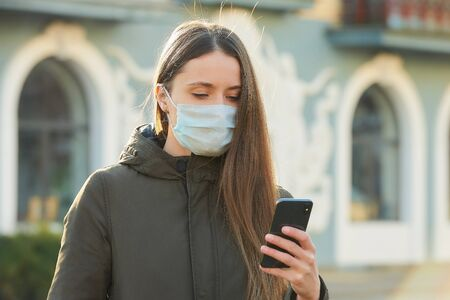 A woman using a smartphone wears a medical face mask to avoid the spread coronavirus on a street. A girl with a surgical mask on the face against COVID-19.