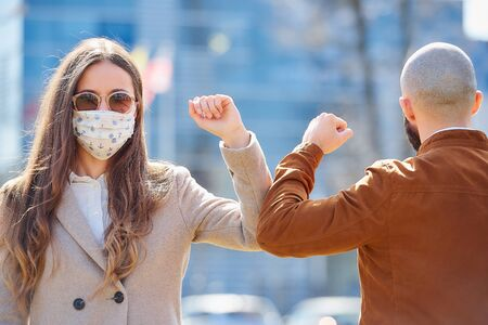 Elbow bumping. Elbow greeting to avoid the spread of coronavirus (COVID-19). Man and woman meet in the street with hands. Instead of greeting with a hug or handshake, they bump elbows instead.